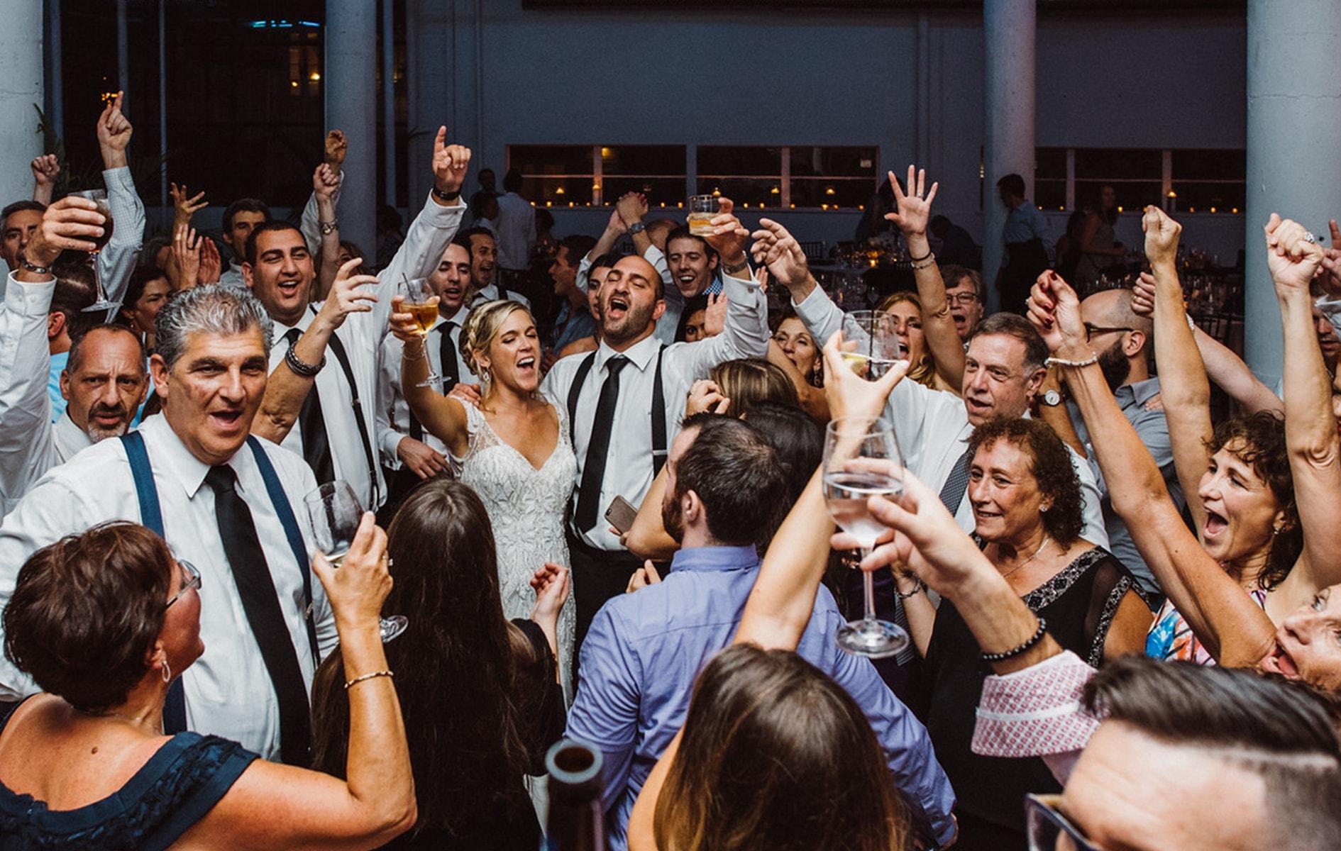 bride and groom dancing with friends on dance floor