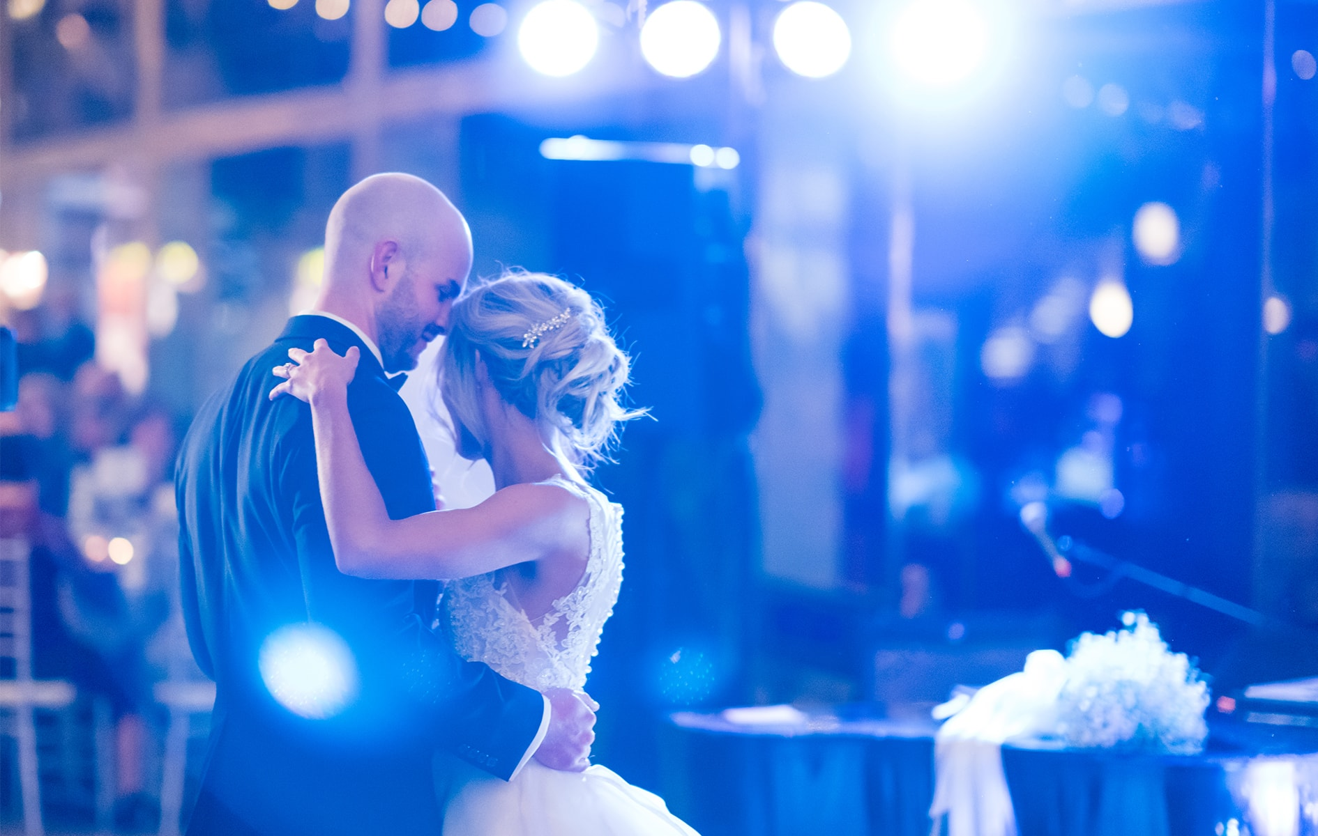 bride and groom dancing under lights at wedding