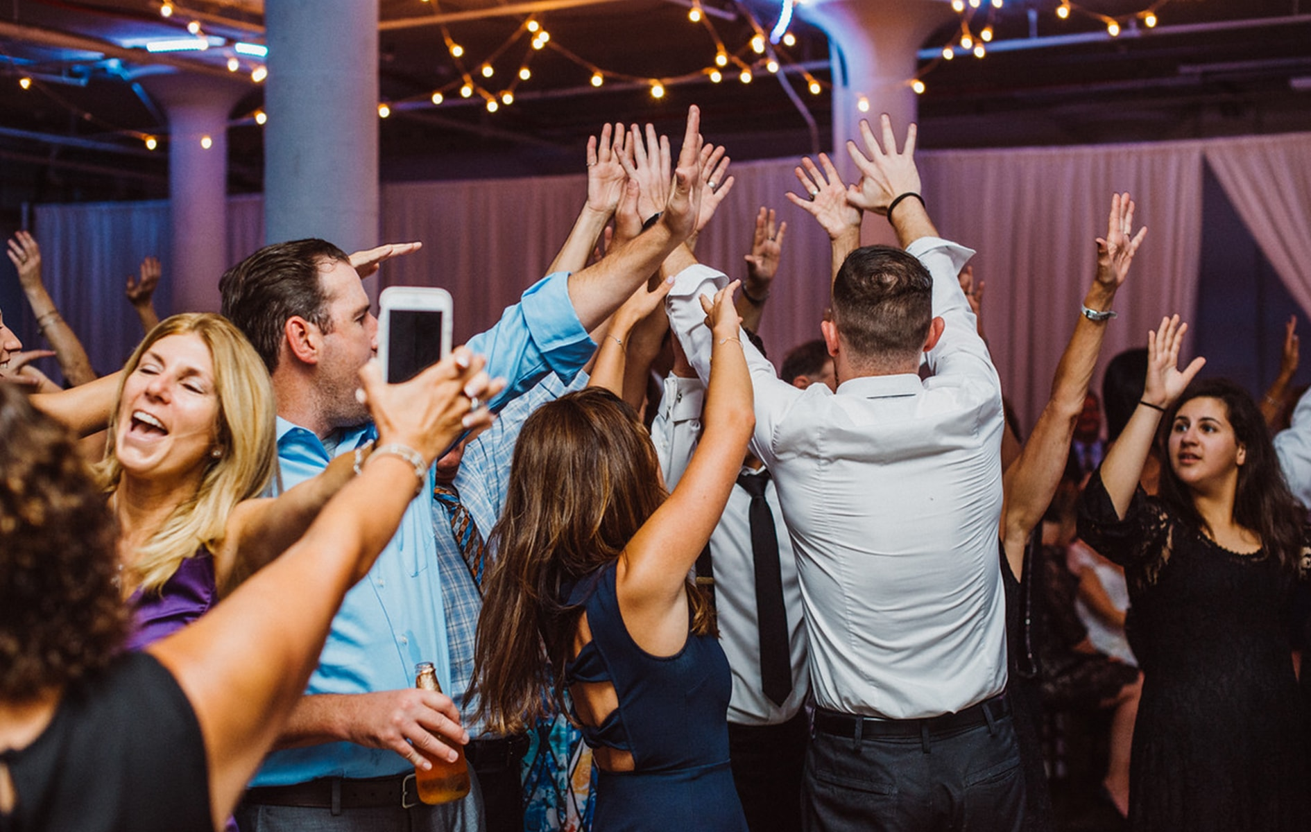 group of friends and guests throwing their hands in the air