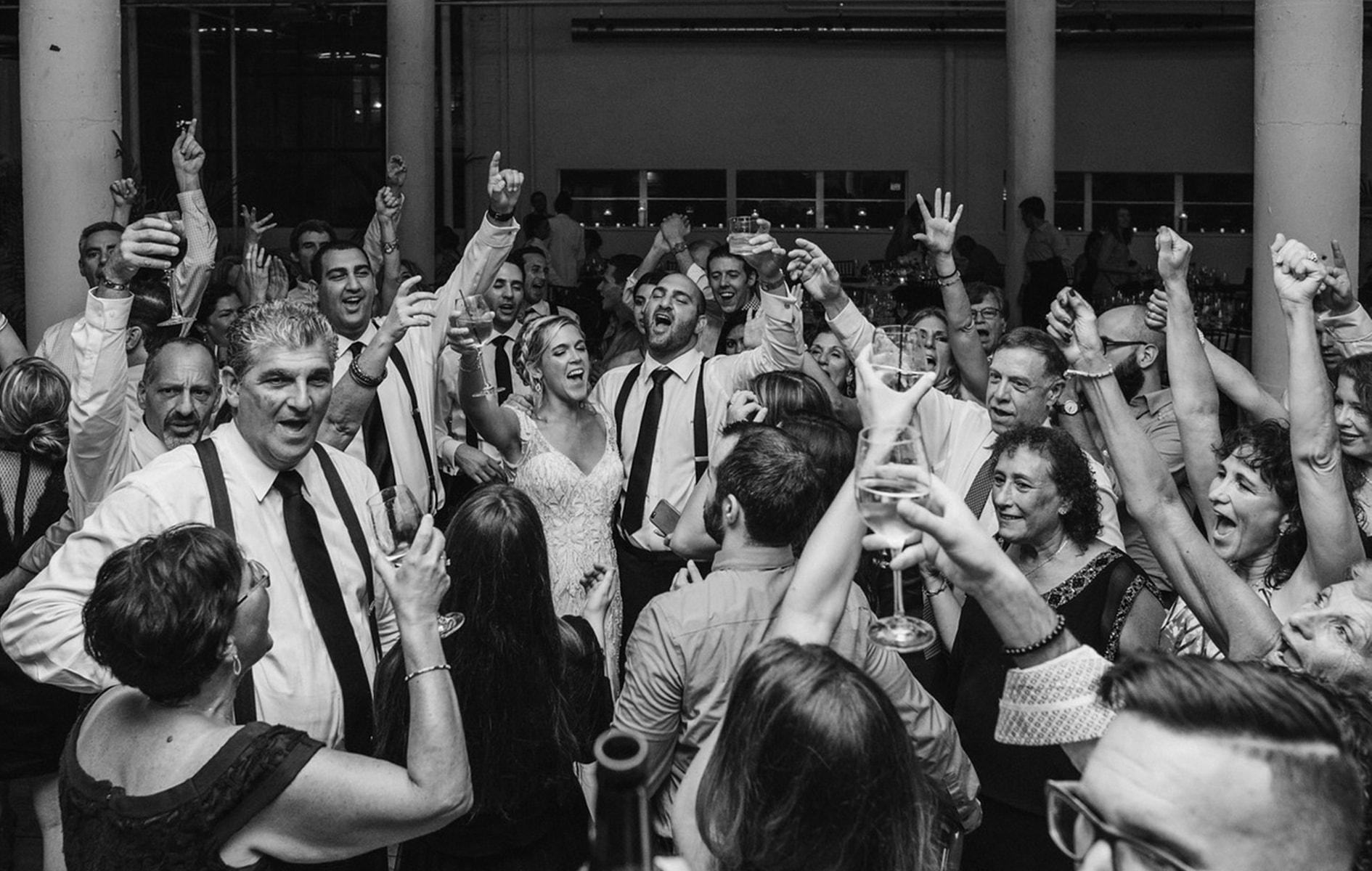 wedding guests cheer on the dance floor